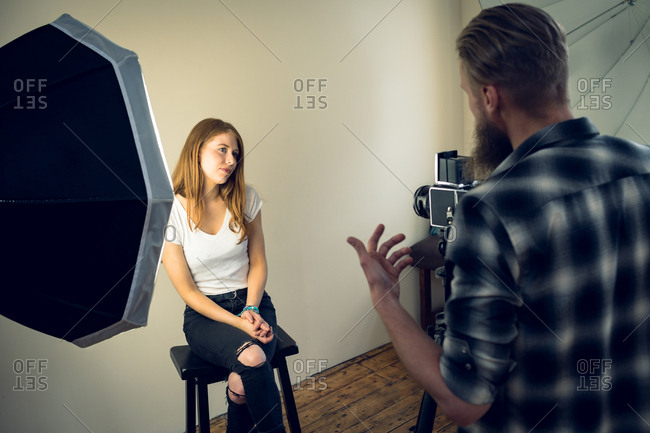 Rear view of photographer talking to fashion model while photographing in studio