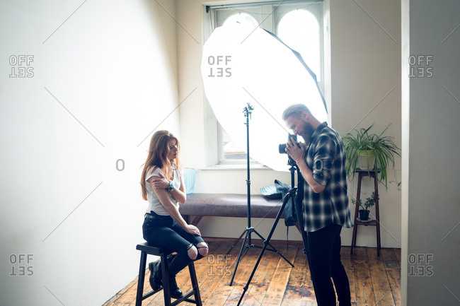 Side view of photographer photographing female fashion model while photographing in studio