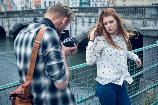 Photographer photographing fashion model while standing by river in city