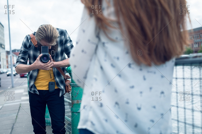 Photographer photographing fashion model while standing on footpath in city