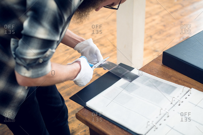 High angle view of photographer cutting film reel while working in studio
