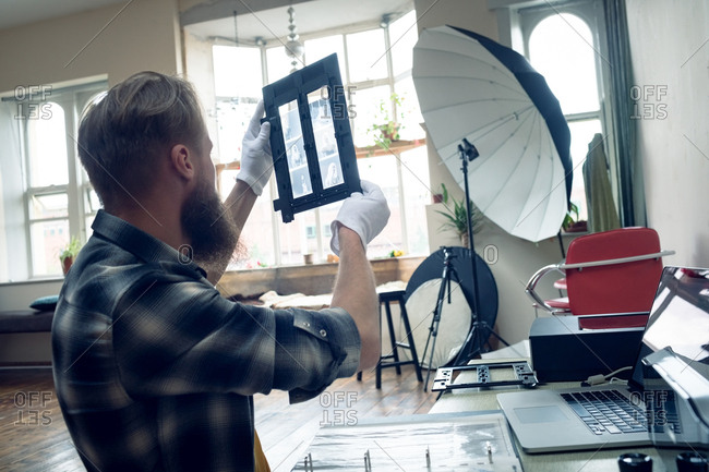 Side view of photographer looking at negatives in frame while sitting at table