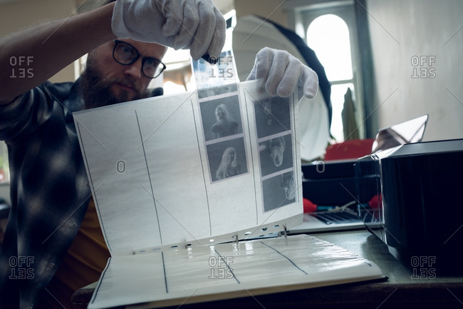Photographer putting negatives in folder while sitting at table