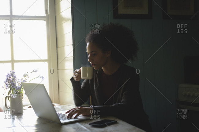 Woman drinking coffee using laptop while sitting on table at home