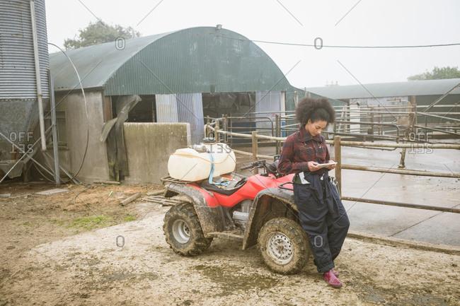 Beautiful female farmer using digital tablet in field
