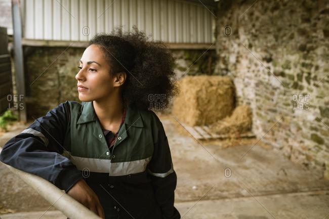 Thoughtful female farmer relaxing in barn