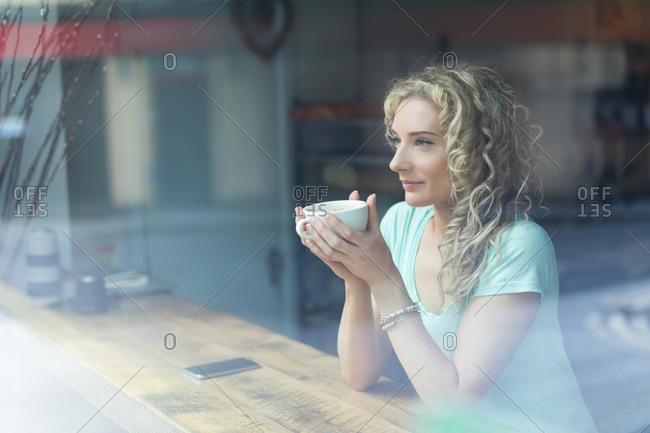 Smiling woman looking away while sitting in cafe seen through window at cafe
