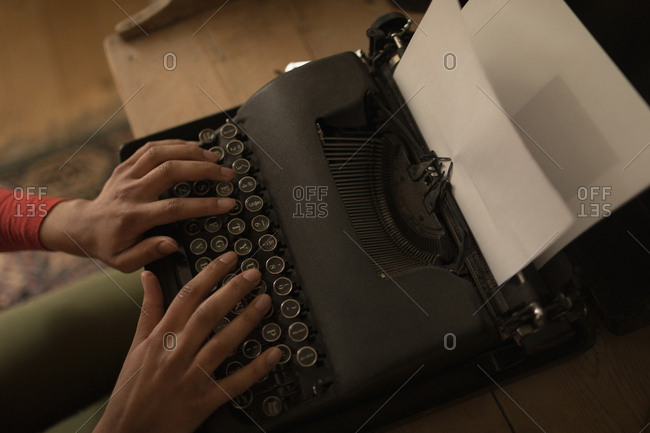 Mid-section of woman working on typewriter at home