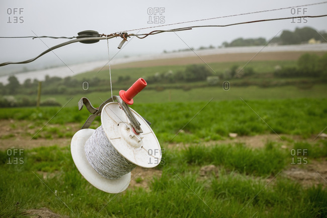 Spool of wire hanging  on wire in field