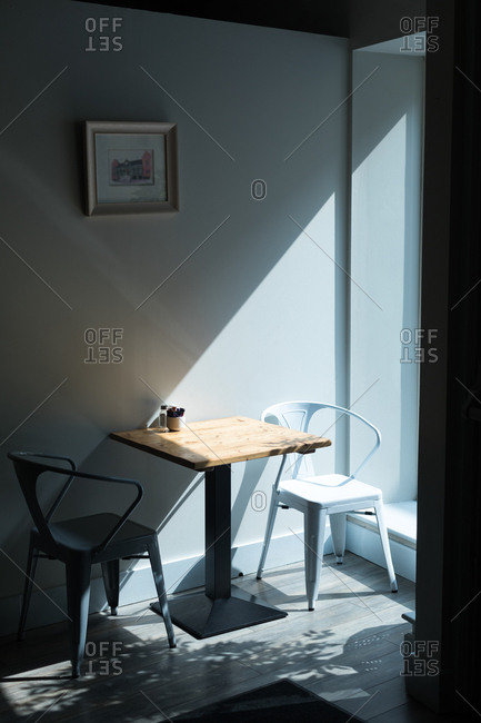 Empty chair at table by wall in cafe