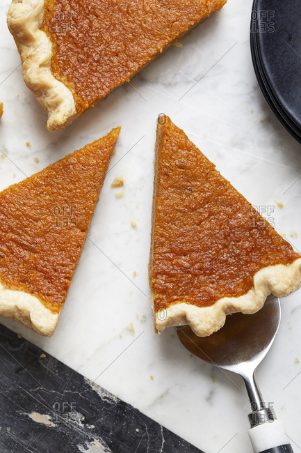 Slices of pumpkin pie on marble counter