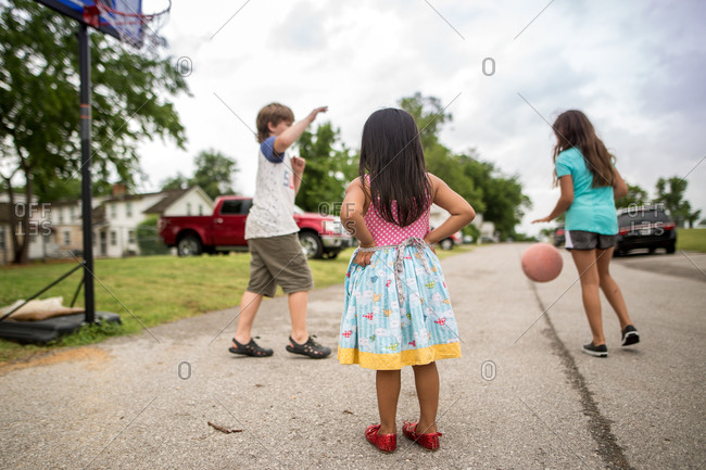 Little girl watches two older siblings play basketball in street