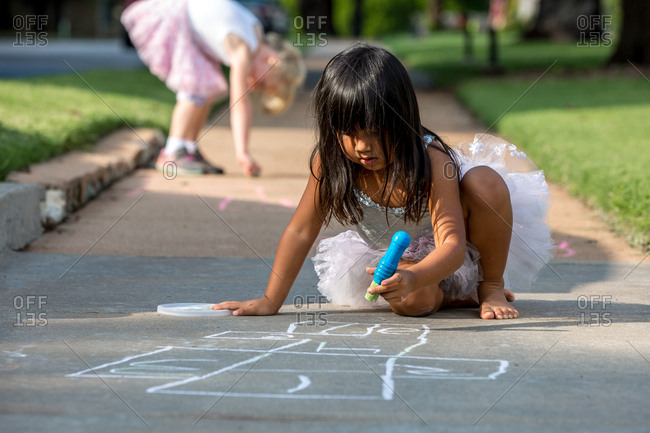 Young girls drawing with sidewalk chalk