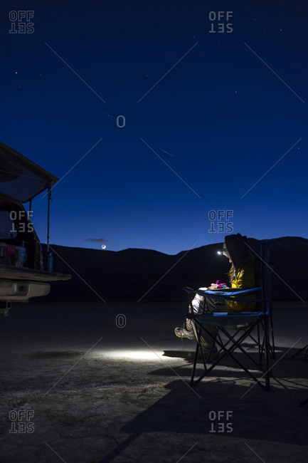 Female hiker using headlamp at night while sitting on camping chair