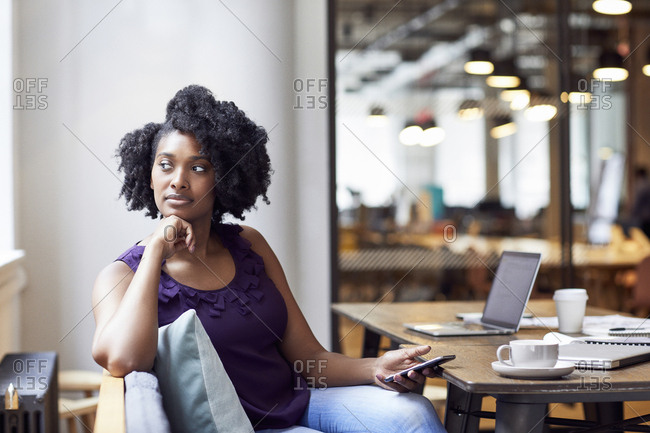 Thoughtful businesswoman looking away while holding smart phone in office