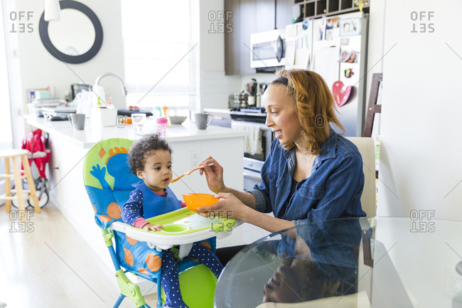 Mother feeding daughter while sitting at table