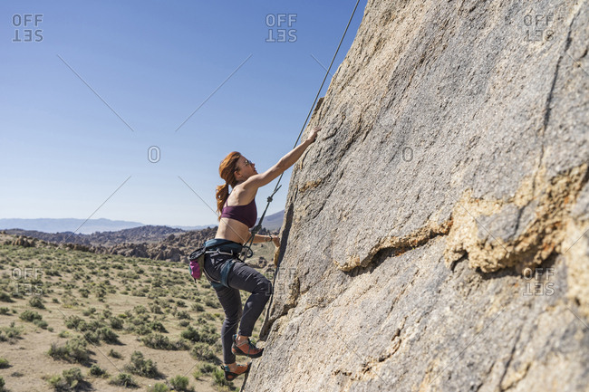 side view of female hiker climbing on mountain stock photo offset