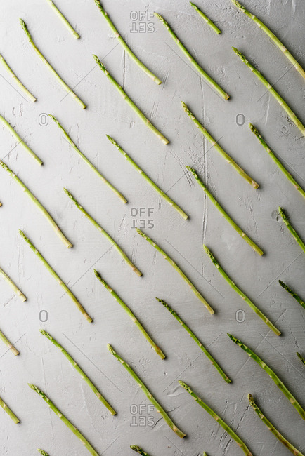 Food art. Top view of raw asparagus sticks laid out in a creative way on concrete background