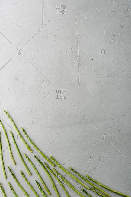 Food inspiration. Directly above view of asparagus river flowing on concrete background, copy space