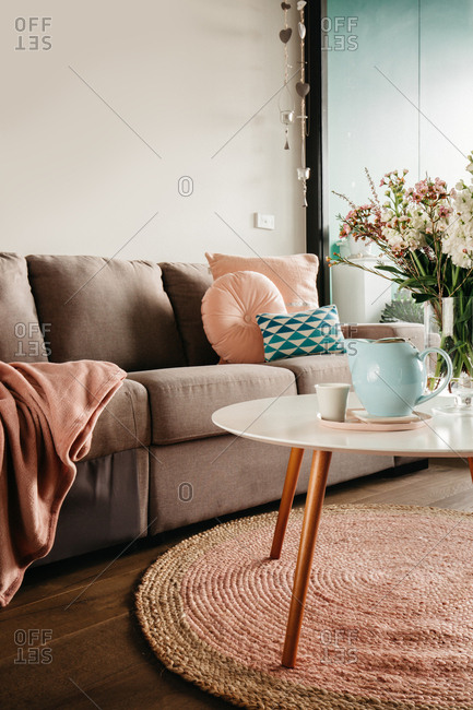 Pretty feminine apartment with pastel blue teapot and pink soft furnishings