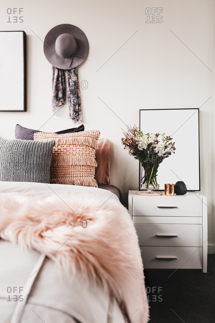 Pretty boho styled bedroom with fresh cut flowers and pink sheepskin