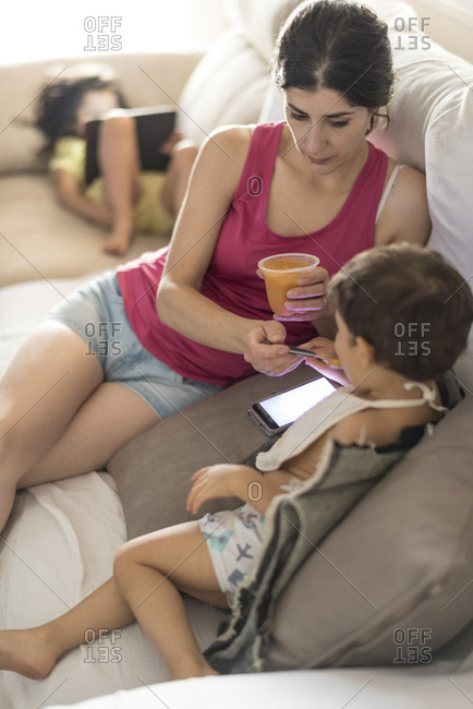 Mother feeding fruit to baby with smartphone help, sister in background