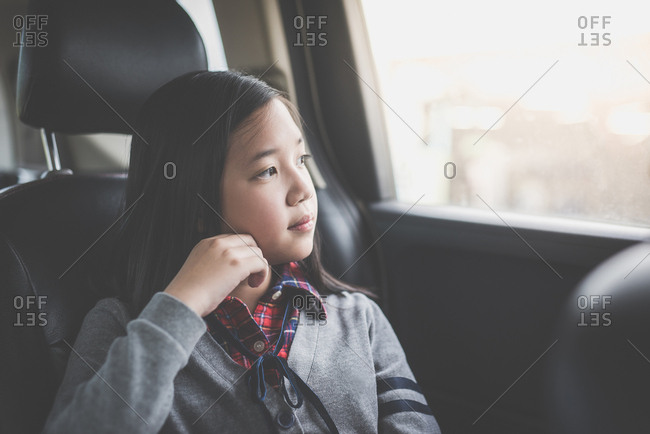 Beautiful Asian girl looking through window while travels by car