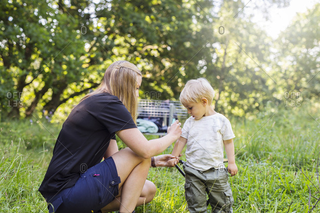 Mother spraying son (2-3) with insect repellant