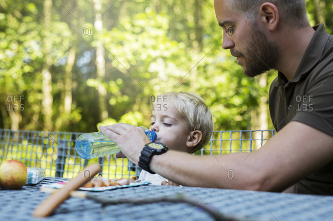 Boy (2-3) drinking water by picnic table