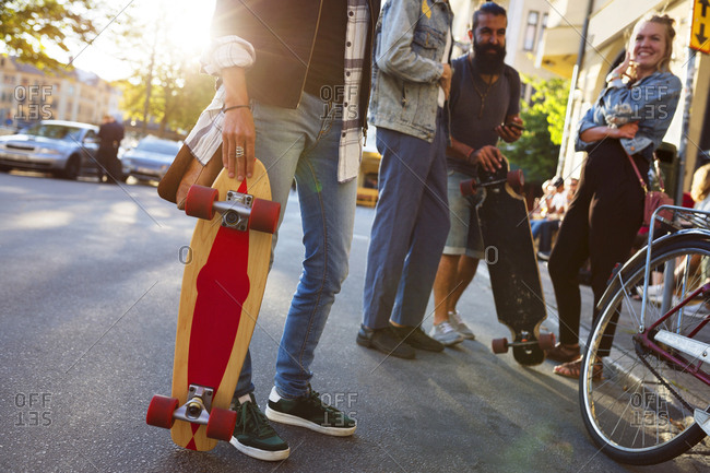 Friends standing with longboards and bicycles
