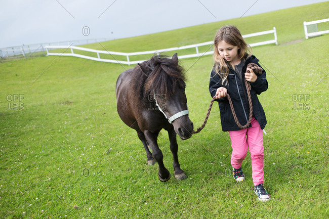 Girl (4-5) walking with pony