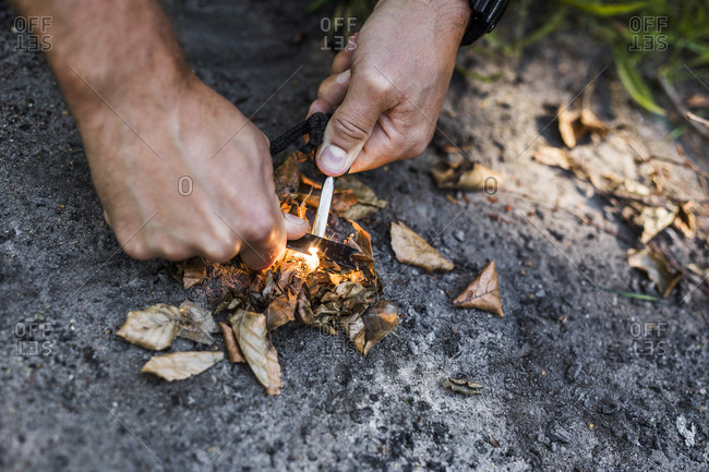 Man igniting camp fire