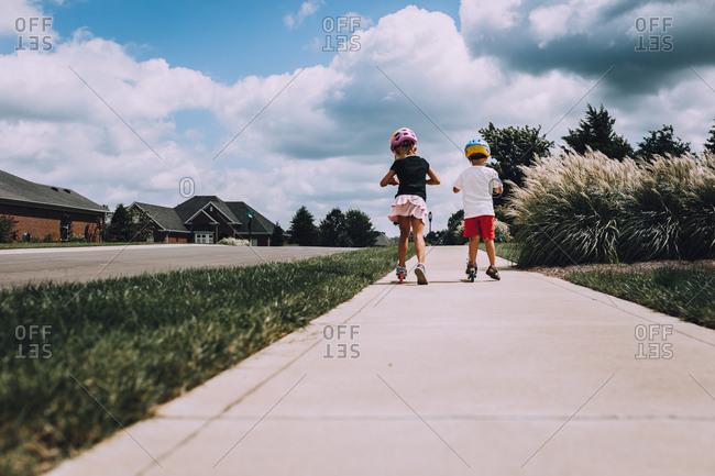 Kids riding scooters on sidewalk