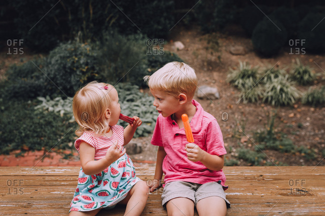 Kids talking while eating popsicles outside