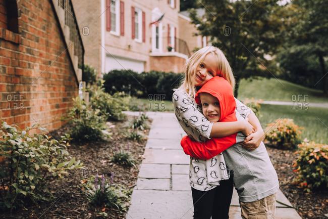 Boy and girl hugging on sidewalk