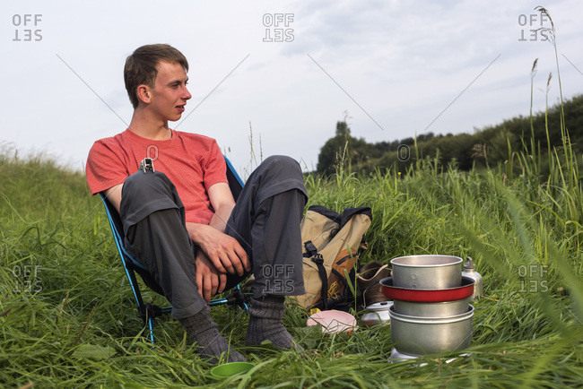 Teen man sitting in chair with camping stove enjoying nature