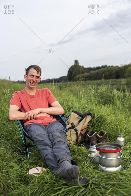 Happy young man sitting in chair with camping stove in field