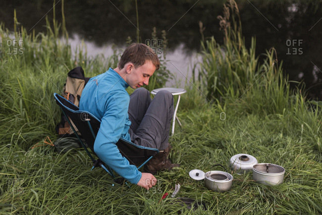 Teen man sitting at waterfront with camping stove