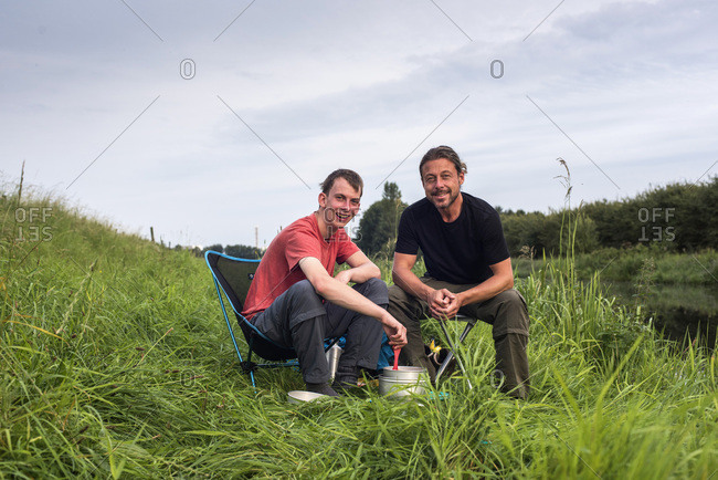 Happy two men preparing food on camping stove while sitting in nature