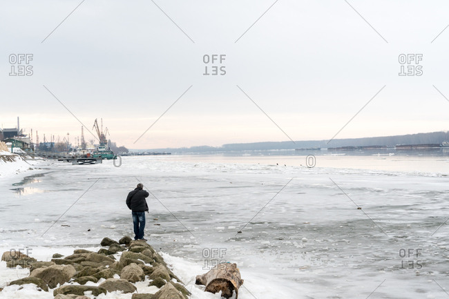 Man looking at the frozen Danube River with floating and thick ice in Bulgaria