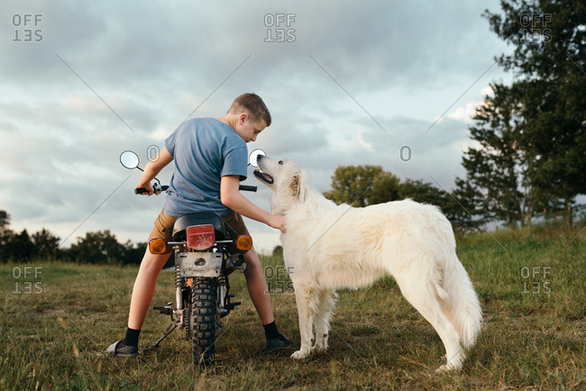 Boy sitting on dirt bike petting large white dog