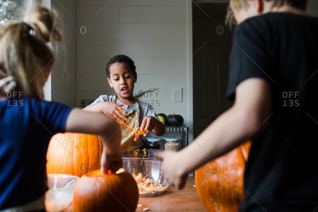 Children carving pumpkins together