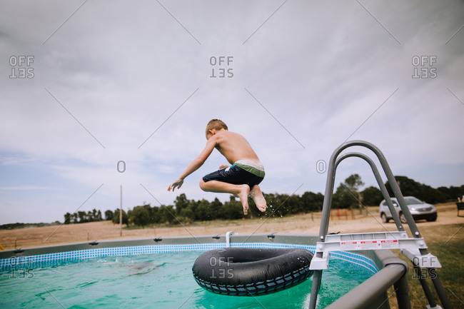 A boy jumping onto a pool inflatable pool toy