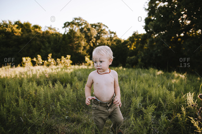 A toddler boy standing outside