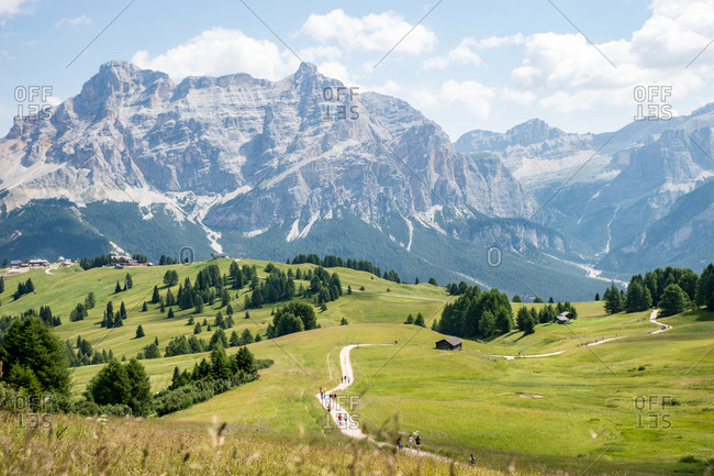 Italy, Val Gardena - July 19, 2015: Hikers in the Val Gardena with the Dolomite Mountains in the background