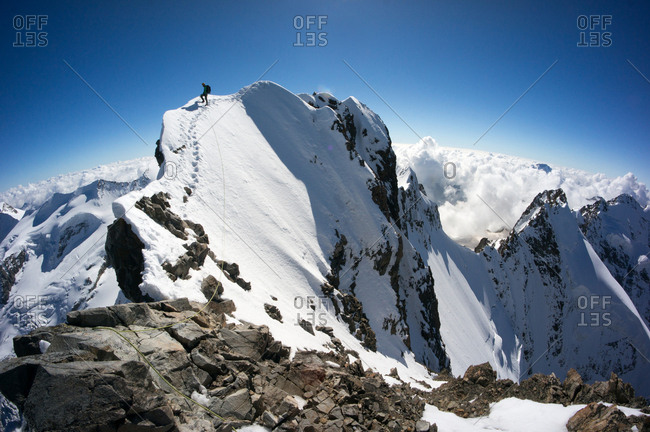Switzerland, Piz Bernina - October 4, 2014: A Mountaineer is exploring the beautiful Piz Bernina, which is the highest point of the Bernina Range and the highest mountain in the Eastern Alps. The mountain is located south of Pontresina and near the major Alpine resort of St. Moritz, in the Engadin valley