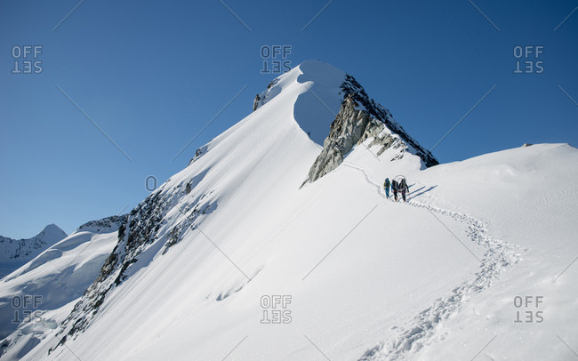 Switzerland, Piz Bernina - October 4, 2014: Mountaineers exploring the beautiful Piz Bernina, which is the highest point of the Bernina Range and the highest mountain in the Eastern Alps. The mountain is located south of Pontresina and near the major Alpine resort of St. Moritz, in the Engadin valley