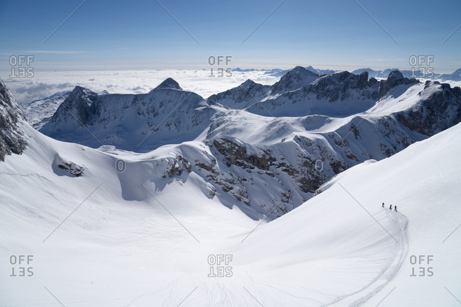 Austria, Styria - March 13, 2015: Three skiers in a valley of the Dachstein mountain in Styria
