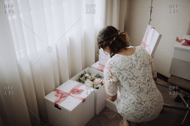 Woman opening a box containing a bridal bouquet