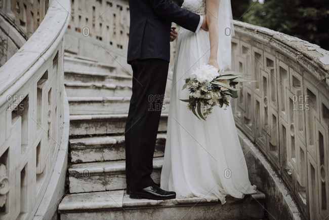 Groom standing on staircase next to bride holding wedding bouquet